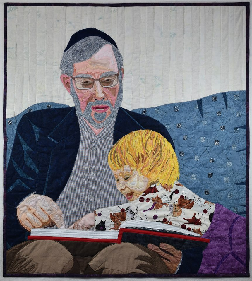 quilt design showing father and little girl reading a book