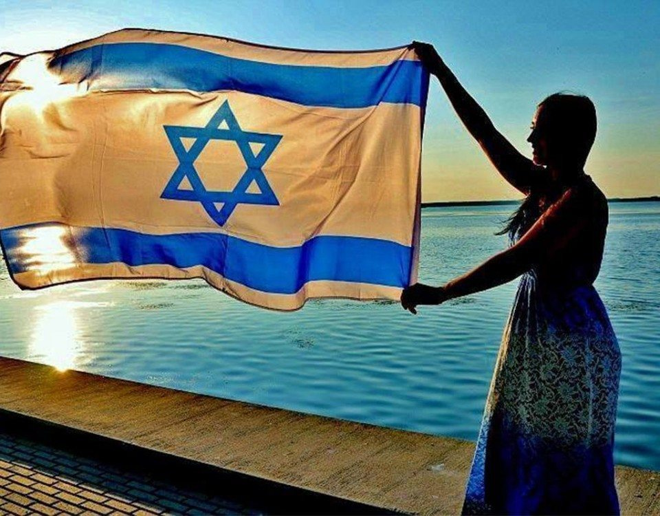 Woman waves Israei flag with a view of the sea