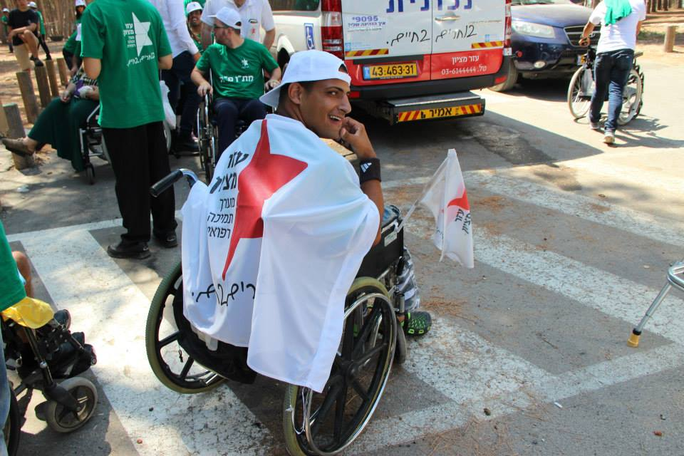 Ezer Mizion special needs summer campgoer in wheelchair with flag