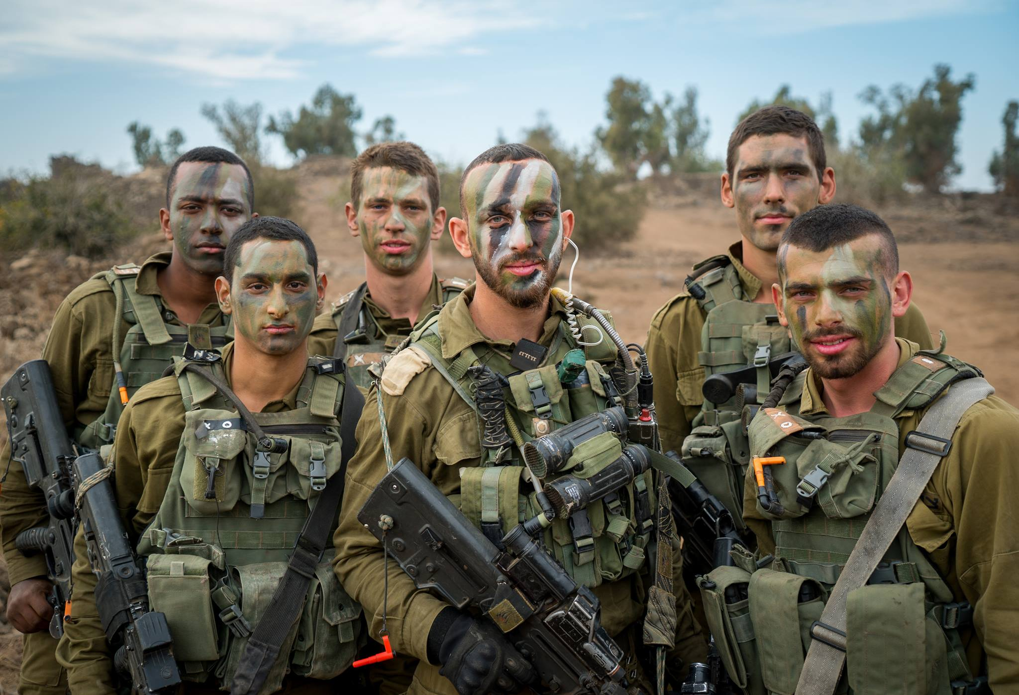 A group of IDF soldiers with full gear and war painted faces